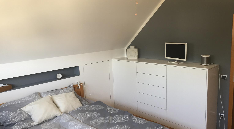 Effiziente Platznutzung der Dachschräge hinter dem Bett