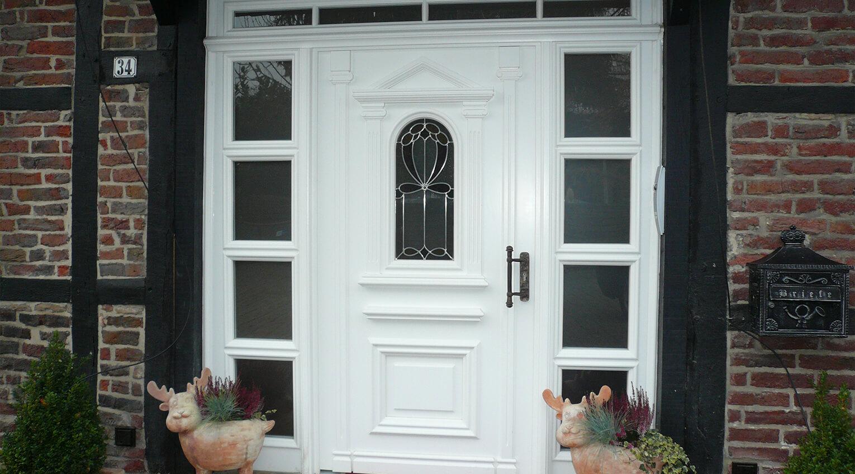 Haustür in großzügiger Einfassung und viel Glas für einen hellen Eingangsbereich
