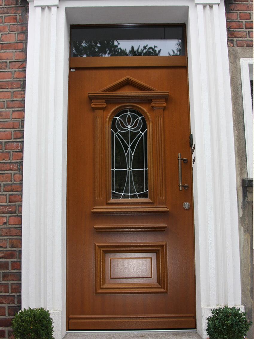 Haustür aus Holz mit Oberlicht, passend zur klassischen Einfassung