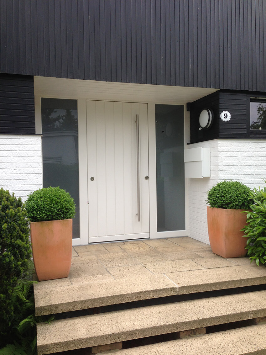 Moderne Haustür mit zwei lichtdurchlässigen Seitenteilen für eine moderne Ästhetik